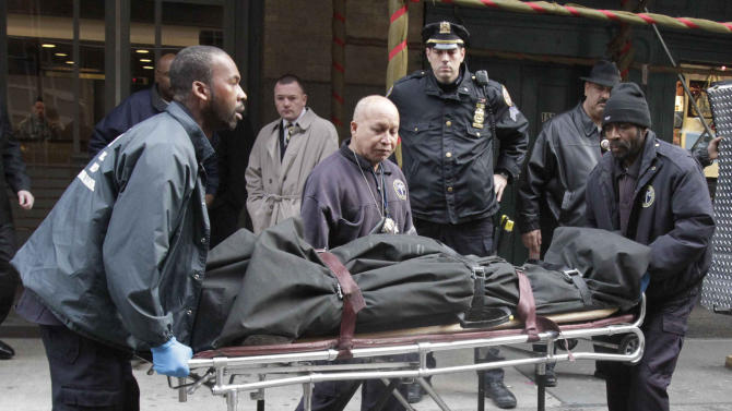 """Medical examiner staff remove the body of Mark Madoff from the apartment building in which he lived, Saturday, Dec. 11, 2010 in the Soho neighborhood of New York. Mark Madoff, the eldest son of disgraced financier Bernard Madoff, hanged himself by a dog leash in his apartment Saturday after two years of """"unrelenting pressure"""" following his father's arrest in a multibillion-dollar fraud that enveloped the entire family, law enforcement officials and a family attorney said. (AP Photo/Mary Altaffer)"""