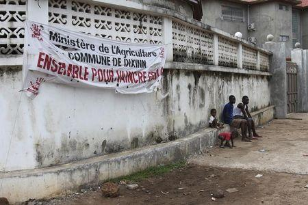 People sit under a banner outside the Ministry of Agriculture building in Conakry, Guinea