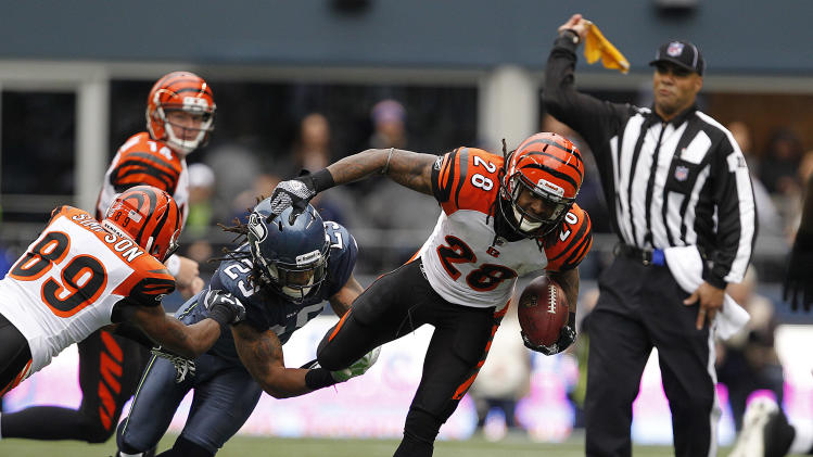Seattle Seahawks' Earl Thomas (29) gets a hand on Cincinnati Bengals' Bernard Scott (28) as a referee throws a flag during the first half of an NFL football game, Sunday, Oct. 30, 2011, in Seattle. (AP Photo/Elaine Thompson)