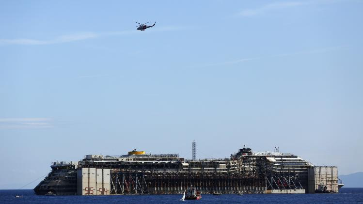 A military helicopter flies over the cruise liner Costa Concordia during refloat operation maneuvers at Giglio Island