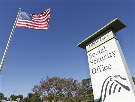 An American flag flutters in the wind next to signage for a U.S. Social Security Administration office in Burbank