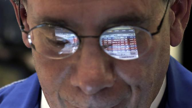 The glasses of trader Sal Suarino reflect the screen of his handheld device, as he works on the floor of the New York Stock Exchange Tuesday, March 5, 2013. The Dow is closing at a record, beating the previous high it set in October 2007, before the financial crisis and the Great Recession. (AP Photo/Richard Drew)