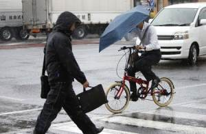 A pedestrian wearing a rain jacket and a man holding an umbrella while riding on a bicycle, cross a street in Tsu, Mie Prefecture, western Japan