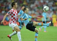 Croatian midfielder Ivan Perisic (L) challenges Spain's Andres Iniesta during their Euro 2012 on June 18. Spain defeated Croatia 1-0 to top the group and leave the Croatians to take an early flight home