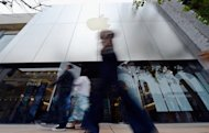 Customers and pedestrians walk in front of the Apple store at The Grove on January 23, 2013 in Los Angeles, California. A US federal judge blocked Friday an Apple shareholder vote in response to a hedge fund lawsuit that claimed the tech giant was improperly bundling questions on a ballot