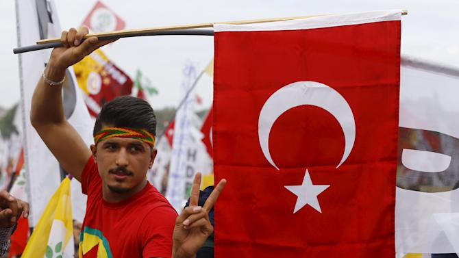 Supporter of Demirtas, co-chairman of the pro-Kurdish People's Democracy Party, gestures while holding a Turkish national flag during an election rally ahead of Turkey's June 7 parliamentary elections in Istanbul