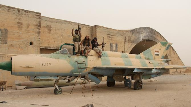 Members of Al-Qaeda's Syrian affiliate and its allies sit on a Syrian army MiG-21 fighter jet after they seized the Abu Duhur military airport on September 9, 2015