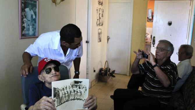 Conrado Marrero, the world's oldest living former major league baseball player, holds up a Washington Senator team photo, while a former teammates takes a photo, during Marrero's 102nd birthday celebration at his home in Havana, Cuba, Thursday, April 25, 2013. In addition to his longevity, the former Washington Senator has much to celebrate this year. After a long wait, he finally received a $20,000 payout from Major League baseball granted to old-timers who played between 1947 and 1979. The money had been held up since 2011 due to issues surrounding the 51-year-old U.S. embargo on Cuba, which prohibits most bank transfers to the Communist-run island. But the payout finally arrived in two parts, one at the end of last year, and the second a few months ago, according to Marrero's family. (AP Photo/Franklin Reyes)