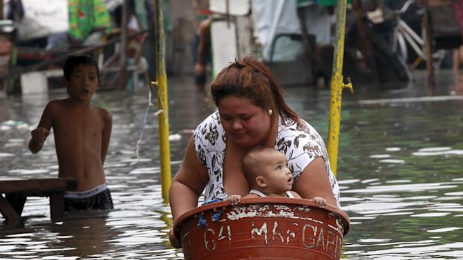 A mother puts her baby in a basin while she wades in waist-deep flooding caused by typhoon Linfa, locally named Egay, at Longos town in Malabon city