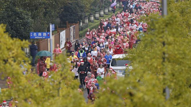Hundreds of runners dressed in Santa outfits compete during a charity Santa run in Shanghai