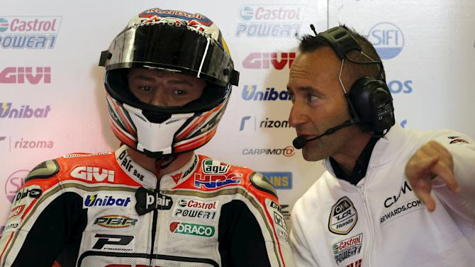 Honda MotoGP rider Miller of Australia talks with a team member in his garage during a free practice session at the Twin Ring Motegi circuit ahead of Sunday's Japanese Grand Prix in Motegi,