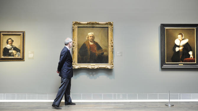 """This May 30, 2012 photo shows Museum of Fine Arts, Houston curator Edgar Peters Bowron passing Rembrandt's """"Portrait of the Artist"""", center, as he looks over some of the paintings from London's Kenwood House at the museum in Houston. The collection of paintings including works by Rembrandt, Van Dyck and Gainsborough has left its home to travel the U.S. while the stately mansion on Hampstead Heath undergoes renovation. The exhibit opens June 3. (AP Photo/Pat Sullivan)"""