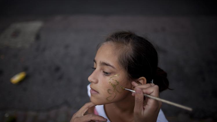 "Sol Basualdo, a member of the murga ""Los amantes de La Boca,"" has her makeup done in preparation for carnival celebrations in Buenos Aires, Argentina, Saturday, Feb. 2, 2013. Argentina's carnival celebrations may not be as well-known as the ones in neighboring Uruguay and Brazil, but residents of the nation's capital are equally passionate about their ""murgas,"" or traditional musical troupes. The murga ""Los amantes de La Boca,"" or ""The Lovers of The Boca"" is among the largest, with about 400 members. It's a reference to the hometown Boca Juniors, among the most popular soccer teams in Argentina and the world. (AP Photo/Natacha Pisarenko)"
