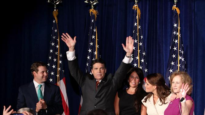 Texas Gov. Rick Perry, surrounded by his family, waves to the crowd after announcing his run for president, Saturday, Aug. 13, 2011 in Charleston, S.C. (AP Photo/Alice Keeney)
