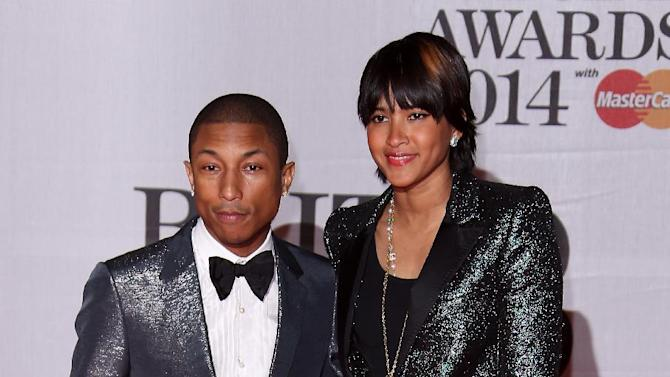 US singer-songwriter Pharrell Williams, left and his wife Helen Lasichanh arrive at the BRIT Awards 2014 at the O2 Arena in London on Wednesday, Feb. 19, 2014. (Photo by Joel Ryan/Invision/AP)