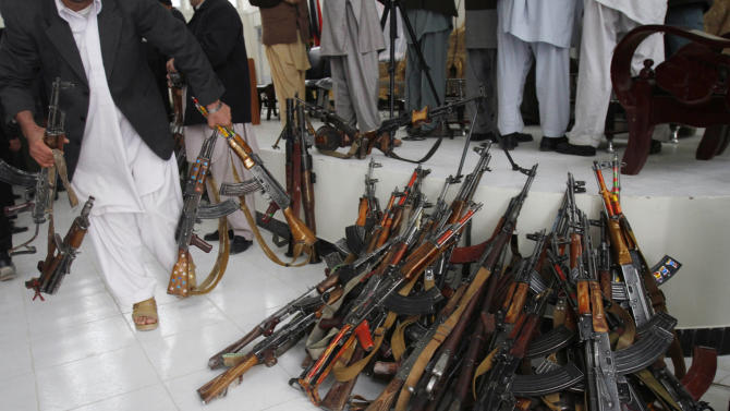 An Afghan official gathers the weapons of former Taliban militants during a joining ceremony with the Afghan government in Mehterlam, Laghman province, east of Kabul, Afghanistan, Monday, March 12, 2012. About 200 former Taliban militants from Laghman province handed over their weapons as part of a peace-reconciliation program. (AP Photo/Rahmat Gul)
