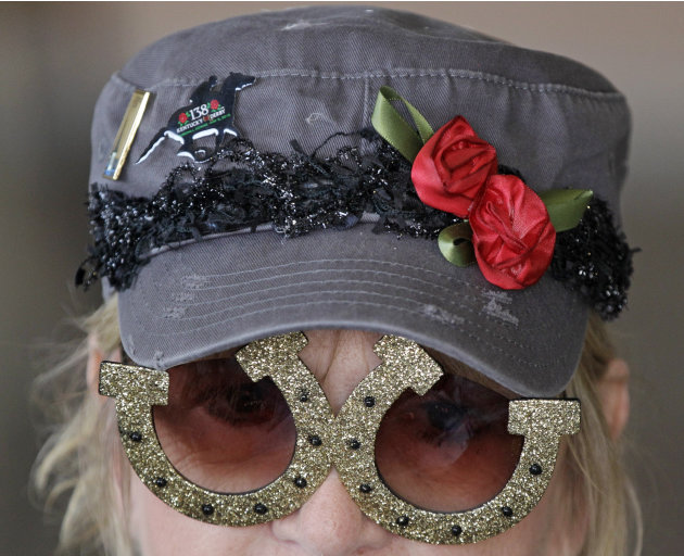 Sandy Cousins, of Fond du Lac, Wis., wears horseshoe glasses while waiting for the 138th Kentucky Derby horse race at Churchill Downs, Saturday, May 5, 2012, in Louisville, Ky.  The Run for the Roses