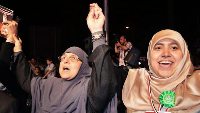 In this Saturday, May 12, 2012 photo, the wife of then Presidential candidate Mohammed Morsi, Naglaa Ali Mahmoud, left, attends a rally during his campaign in Cairo, Egypt. Egypt's new first lady Naglaa Ali Mahmoud and her predecessor Suzanne Mubarak have at least one thing in common: Both have seen their husbands and sons detained in Egyptian prisons. The similarities may end there though. Suzanne Mubarak was often criticized as being vain, self-important and strong-willed _ propelling her son, Gamal, toward inheriting the presidency. But the wife of Islamist President-elect Mohammed Morsi is a conservative, religious Muslim who wears the veil and appears to be extremely modest. (AP Photo/Ahmad Hammad)