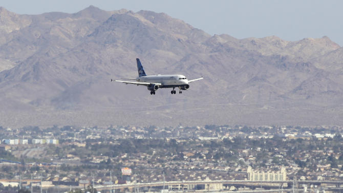 "Jet Blue flight 191 from New York makes its approach to McCarran International Airport, Tuesday, March 27, 2012, in Las Vegas. The captain of the plane stormed through his plane rambling about a bomb and threats from Iraq on Tuesday until passengers on the Las Vegas-bound flight tackled him to the ground just outside the cockpit, passengers said. The captain was taken to a hospital after suffering a ""medical situation"" on board that forced an emergency landing in Amarillo, Texas, the airline said. (AP Photo/Julie Jacobson)"