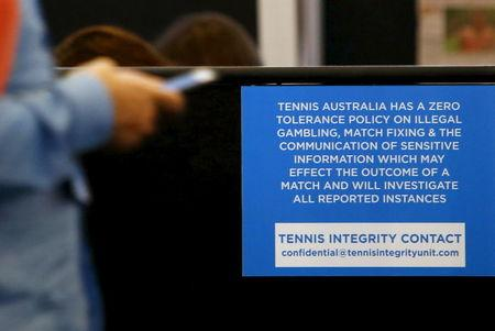 A man uses his phone next to a sign displaying the contact for the Tennis Integrity Unit at the Australian Open tennis tournament at Melbourne Park