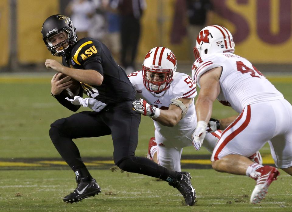 Arizona State's Taylor Kelly, left, is taken down by Wisconsin's Joe Schobert (58) and Chris Borland (44) in the first half of an NCAA college football game on Saturday, Sept. 14, 2013, in Phoenix. (AP Photo/Ross D. Franklin)