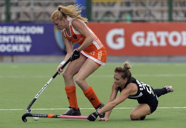 The Netherlands' Margot Van Geffen (L) vies for the ball with New Zealand's Charlotte Harrison during their Champions Trophy 2012 quarterfinals field hockey match in Rosario, Santa Fe, Argenti