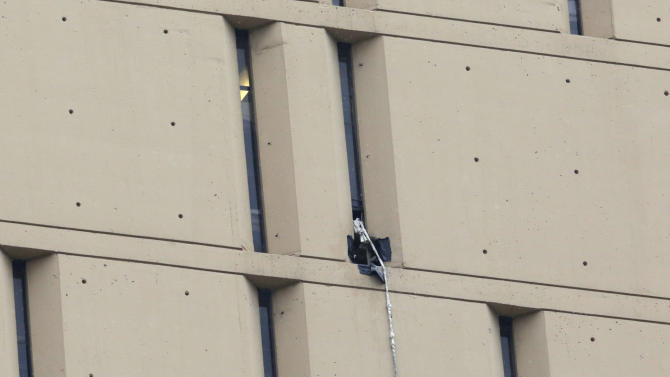 A rope dangles from a window on the back side of the Metropolitan Correctional Center Tuesday, Dec. 18, 2012, in Chicago. Two convicted bank robbers used a knotted rope or bed sheets to escape from the federal prison window high above downtown Chicago early Tuesday, a week after one of them made a courtroom vow of retribution, to federal judge. The escape occurred sometime between 5 a.m. and 8:45 a.m. when the inmates were discovered missing, Chicago Police Sgt. Mark Lazarro said. Hours later, what appeared to be a rope, knotted at six-foot intervals, could be seen dangling into an alley from a window of the Metropolitan Correctional Center approximately 20 stories above the ground. (AP Photo/M. Spencer Green)