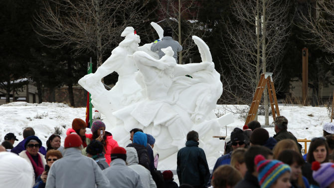 The Mongolian Warriors snow sculpture made by Team Mongolia shows the marble like statue as people view it in the outdoor gallery at the Riverwalk Center during the 23 annual International Snow Sculpture Championships in Breckenridge, Colo., on Friday, Jan. 25, 2013. Each of the 15 sculpture started out of a 12 foot tall, 20-ton block of compacted snow at the outdoor art gallery. The sculptures will remain on display through Feb. 3, 2013, weather permitting. Visit www.gobreck.com for more information. (Nathan Bilow / AP Images for the Breckenridge Resort Chamber)