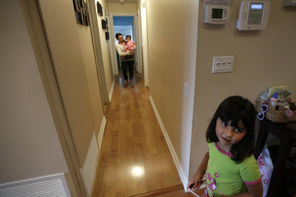 In this Sept. 26, 2012 picture, Domestic worker Alicia Wotherspoon carries Stella Widmann as she begins her day of work at the Widmann home in San Diego. Older daughter Luna Widmann looks on at right.  (AP Photo/Gregory Bull)