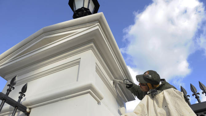 A painter touches up an entrance post outside the White House in Washington, Friday, Jan. 18, 2013, in preparation for this weekend's 57th Presidential Inauguration, where President Barack Obama will be sworn in for a second term. (AP Photo/Susan Walsh)