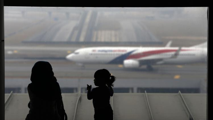 A woman and a girl look at a Malaysia Airlines plane on the tarmac of Kuala Lumpur International Airport