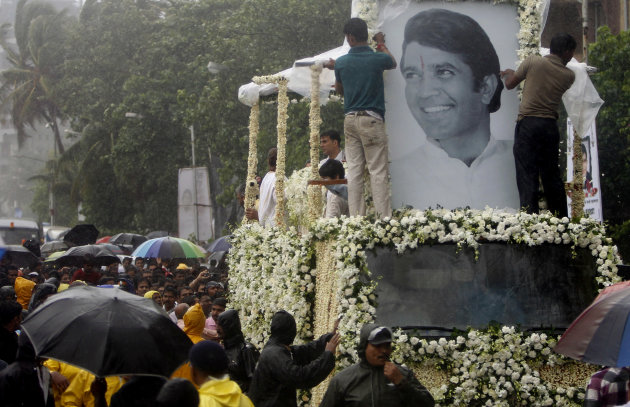 Mourners gather around as the body of Bollywood superstar Rajesh Khanna is taken in a truck during his funeral in Mumbai, India, Thursday, July 19, 2012. Khanna, whose success as a romantic lead in sc
