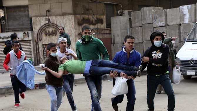 Egyptians carry a protester wounded in clashes with security forces near Tahrir square, where an opposition rally has been called for to voice rejection of President Morsi's seizure of near absolute powers, in Cairo, Egypt, Tuesday, Nov. 27, 2012. The Health Ministry said about 444 people have been wounded nationwide, including 49 who remain hospitalized, since the clashes erupted on Friday, according to a statement carried by the official news agency MENA. (AP Photo/Thomas Hartwell)