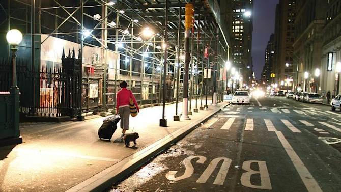 A woman with her luggage and a dog make their way to Wall Street station, to get out of lower Manhattan in New York