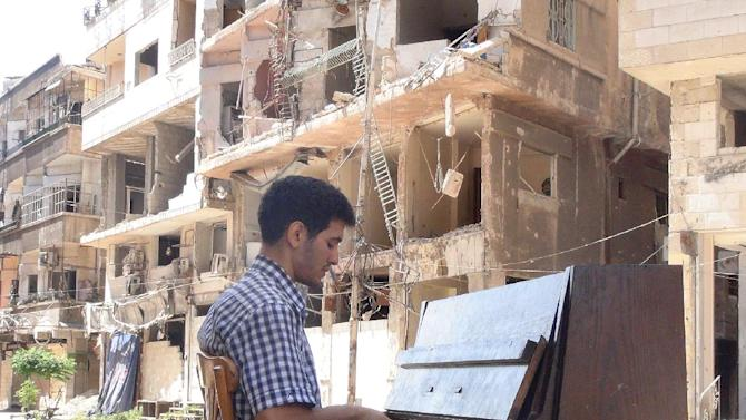 Ayham al-Ahmed, a resident of Damascus' Yarmuk Palestinian refugee camp, plays the piano in the middle of the street near destroyed buildings, on June 26, 2014