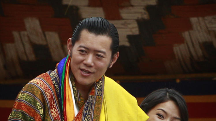 Bhutan's King Jigme Khesar Namgyal Wangchuck, left, and Queen Jetsun Pema greet locals in the crowd at the main stadium as part of their wedding celebrations in Thimphu, Bhutan, Saturday, Oct. 15, 2011. The 31 year-old reformist monarch of the small Himalayan Kingdom wed his commoner bride in a series of ceremonies at a 17th century monastic fortress Thursday. (AP Photo/Kevin Frayer)