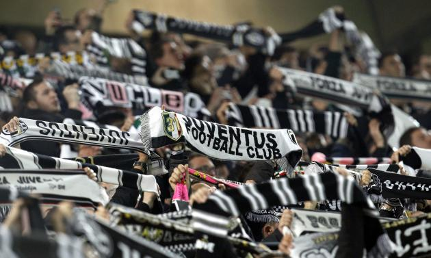 Juventus supporters hold their team flags before the match against Fiorentina in their Europa League round of 16 first leg soccer match at the Juventus stadium in Turin