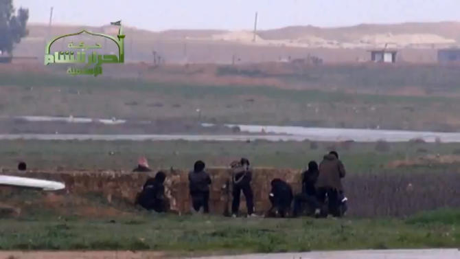 This image taken from video obtained from Ugarit News, which has been authenticated based on its contents and other AP reporting, shows Syrian rebels at Jarrah airfield in Aleppo province, Tuesday, Feb. 12, 2013. Rebels captured a military air base in northern Syria on Tuesday, their second major strategic victory in as many days, activists said.(AP Photo/Ugarit News via AP video)