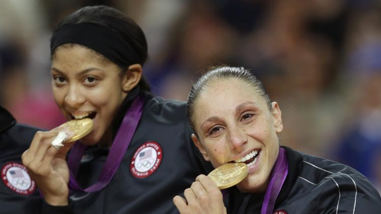 United States' Diana Taurasi, right, and Candace Parker bite their gold medals after beating France in the women's gold medal basketball game at the 2012 Summer Olympics, Saturday, Aug. 11, 2012, in London. (AP Photo/Charles Krupa)