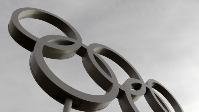 A visitor to Olympic Park stands with a United States flag under a set of Olympic rings at the 2012 Summer Olympics Saturday, Aug. 11, 2012, in London. (AP Photo/Charlie Riedel)