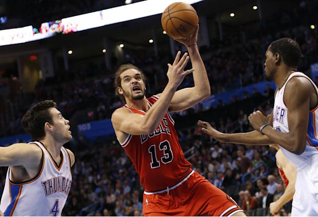 Chicago Bulls center Joakim Noah (13) shoots between Oklahoma City Thunder forwards Nick Collison (4) and Kevin Durant (35) during the first quarter of an NBA basketball game in Oklahoma City, Thursda