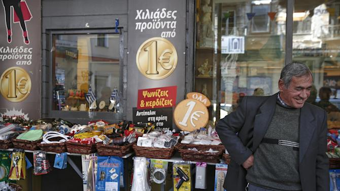 A man checks items at a shop in central Athens, on Monday, April 27, 2015.  Greece has grown isolated in negotiations. With coffers running dry, it had until April 30 to come up with acceptable reforms so creditors can unlock the final 7.2 billion euro ($7.8 billion) bailout installment.  (AP Photo/Yorgos Karahalis)