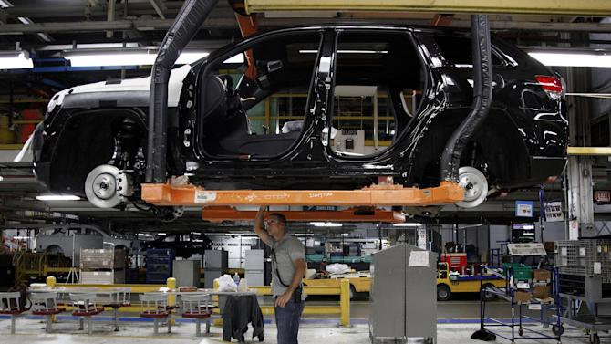In this Wednesday, May 8, 2013, file photo, Jeff Caldwell, 29, right, a chassis assembly line supervisor, checks a vehicle on the assembly line at the Chrysler Jefferson North Assembly plant in Detroit. The government issues its third and final estimate of economic growth in the April-June quarter on Thursday, Sept. 26, 2013. (AP Photo/Paul Sancya, File)