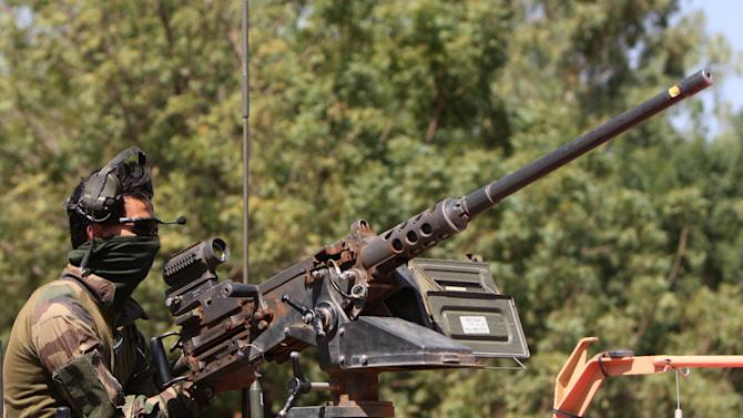 A French soldier mans a machine gun as French troops pass through San in central Mali en route to Sevare, Friday, Jan. 18, 2013. French forces encircled a key Malian town on Friday to stop radical Islamists from striking closer to the capital, a French official said. The move to surround Diabaly came as French and Malian authorities said they had retaken Konna, the central city whose capture prompted the French military intervention last week.(AP Photo/Harouna Traore)