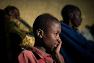 A displaced Congolese boy from Bihumba sits with his family outside a primary school being used for shelter in the village of Kibati on the outskirts of Goma in the Democratic Republic of the Congo&#39;s restive North Kivu province. United Nations helicopters fired on rebel positions in eastern Democratic Republic of Congo after new clashes broke out between rebel fighters and loyalist troops
