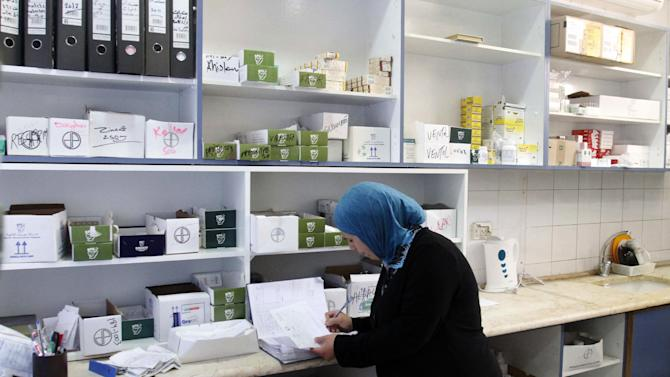 In this Thursday Aug. 16, 2012 photograph, a woman works at the  Ramallah Hospital  pharmacy in the West Bank city of Ramallah. The cash crunch, mainly due to a sharp drop in foreign aid since 2011, is threatening to set off a chain reaction of business failures, layoffs and economic downturn that would undermine one of the West's fundamental strategies toward resolving the Israeli-Palestinian conflict. (AP Photo/Nasser Shiyoukhi)