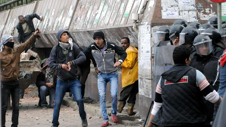 Opponents of Egyptian President Mohammed Morsi clash with Islamist supporters of the president, unseen, as a cordon of riot police separates the groups in Alexandria, Egypt, Friday, Dec. 21, 2012. Thousands of Islamists clashed with their opponents Friday in Egypt's second largest city, Alexandria, on the eve of the second leg of voting on the country's contentious constitution that has deeply polarized the nation.(AP Photo/Ahmed Ramadan)