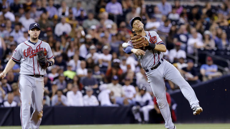 Atlanta Braves' Chris Johnson, left, looks on as shortstop Andrelton Simmons throws to first base but not in time to get San Diego Padres' Tommy Medica in the eighth inning of a baseball game Friday, Aug. 1, 2014, in San Diego. San Diego won the game 10-1.(AP Photo/Don Boomer)