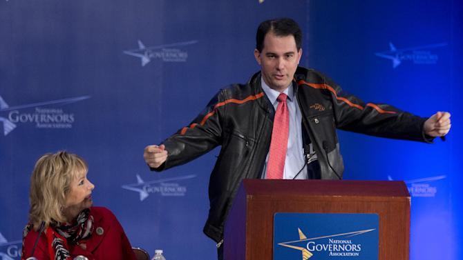 Wisconsin Gov. Scott Walker of Wisconsin, right, puts on his Harley Davidson jacket over his Brewers jersey during the opening session of the National Governors Association 2013 Winter Meeting in Washington, Saturday, Feb. 23, 2013, while NGA Vice Chairman Gov. Mary Fallin of Oklahoma, left, watches.  (AP Photo/Manuel Balce Ceneta)