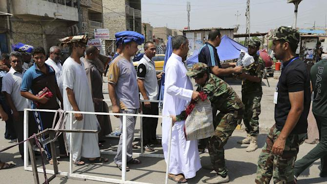 """Iraqi Shiite fighters with the """"Peace Brigades"""" search Shiite worshipers before open-air Friday prayers in the Shiite stronghold of Sadr City, Baghdad, Iraq, Friday, Aug 29, 2014. (AP Photo/Karim Kadim)"""